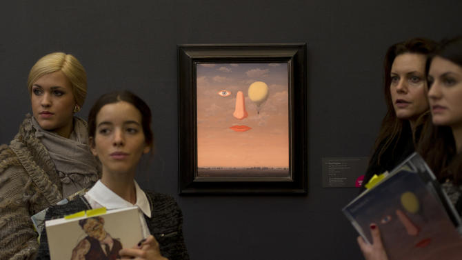 Four women look round as they take notes next to a painting by Rene Margritte entitled Les Belles Relations during a press preview at Sotheby's auction house in London, Thursday, Jan. 31, 2013.  The work is estimated to sell for some 2-3 million pounds (US $ 3.16-4.7 million, euro 2.33-3.5 million) when sold at auction on Feb. 5, in London. (AP Photo/Alastair Grant)