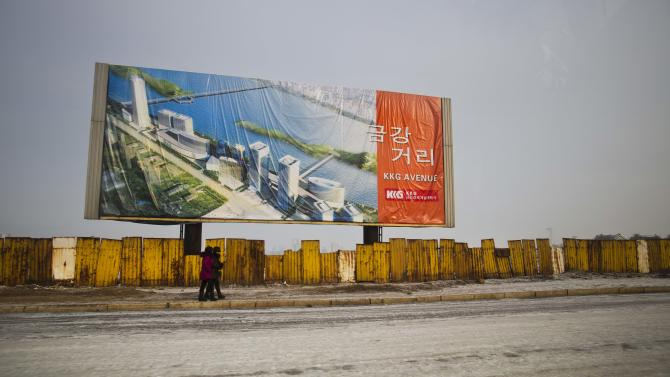 In this Jan. 11, 2013 photo, a billboard showing a new project under construction stands above the outer fence of the construction site in Pyongyang, North Korea. (AP Photo/David Guttenfelder)