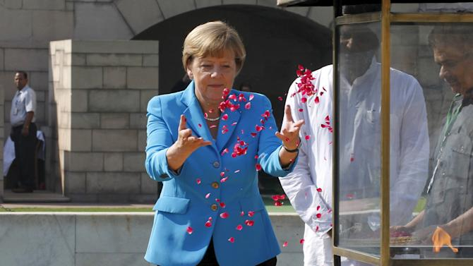 German Chancellor Merkel scatters rose petals at Mahatma Gandhi memorial at Rajghat in New Delhi