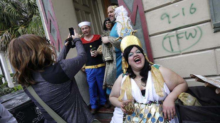 Revelers gather for the start of the Society of Saint Anne walking parade in the Bywater section of New Orleans during Mardi Gras day, Tuesday, Feb. 12, 2013. FEMA markings from Hurricane Katrina are still displayed on the wall. (AP Photo/Gerald Herbert)