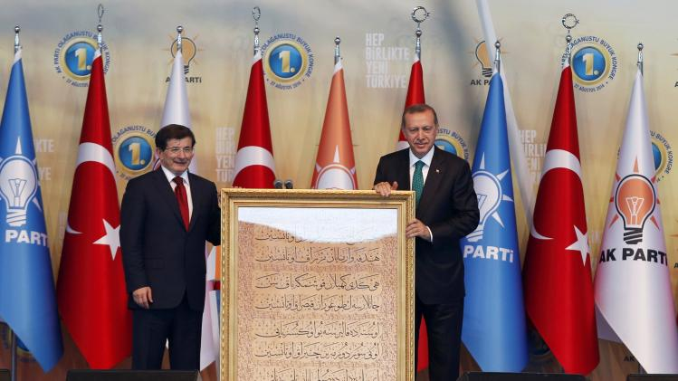 Turkish incoming prime minister Davutoglu presents President-elect Erdogan with a gift during the Extraordinary Congress of the ruling AKP in Ankara