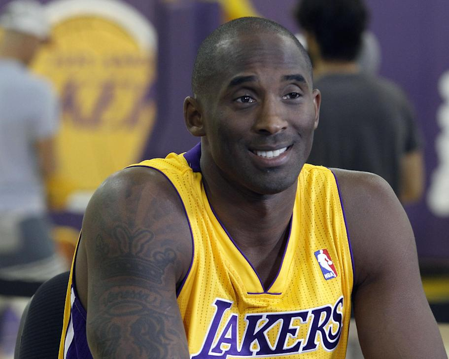 In this Sept. 28, 2013 file photo, Los Angeles Lakers guard Kobe Bryant talks during the NBA basketball teams media day, in El Segundo, Calif. The Lakers have signed Bryant to a 2-year contract extension. General manager Mitch Kupchak made the announcement Monday, Nov. 25, 2013, ending speculation that Bryant could end up with another team after this season