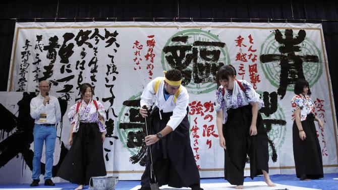 "Astana team rider Nibali of Italy dressed in a hakama writes the Chinese character of ""King"" with a giant brush during a calligraphy performance in Saitama"