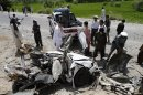 Afghans look at the wreckage of a vehicle after a roadside explosion on the outskirts of Laghman province east of Kabul, Afghanistan, Sunday, Aug. 12, 2011. A provincial spokesman says the roadside bomb has killed a district chief in eastern Afghanistan and three of his bodyguards. (AP Photo/Rahmat Gul)