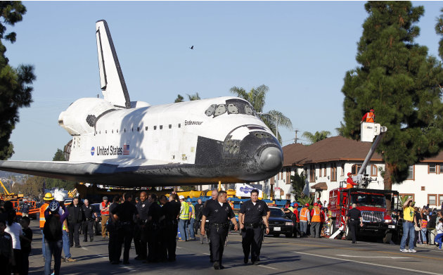 The Space Shuttle Endeavour is slowly moved down Martin Luther King Blvd. in Los Angeles Sunday, Oct. 14, 2012. In thousands of Earth orbits, the space shuttle Endeavour traveled 123 million miles. Bu
