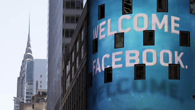 The Chrysler Building is visible behind the animated facade of the Nasdaq MarketSite, welcoming the Facebook IPO, in New York's Times Square,  Friday, May 18, 2012. Facebook's stock is trading up Friday, as investors seek to put a dollar value on the company that turned online social networking into a global cultural phenomenon. (AP Photo/Richard Drew)
