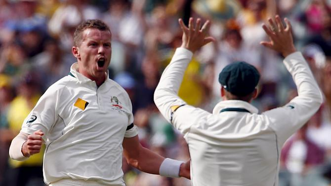 Australia's Peter Siddle celebrates with captain Steve Smith after dismissing New Zealand's Ross Taylor for 21 runs during the first day of the third cricket test match at the Adelaide Oval, in South Australia