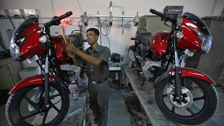 A worker prepares a Bajaj motorcycle before it is delivered to a customer at a Bajaj showroom in Kolkata October 16, 2013. REUTERS/Rupak De Chowdhuri