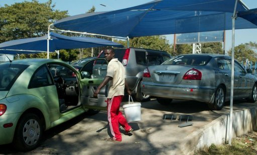 <p>A man cleaning cars on display at a dealership in Harare. In a sign of Zimbabwe's economic recovery from a nearly decade-long crisis, cars are jamming the roads, posing a new headache for cities where a few years ago traffic was so thin that Zimbabweans joked you could lie in the middle of the street without getting run over.</p>