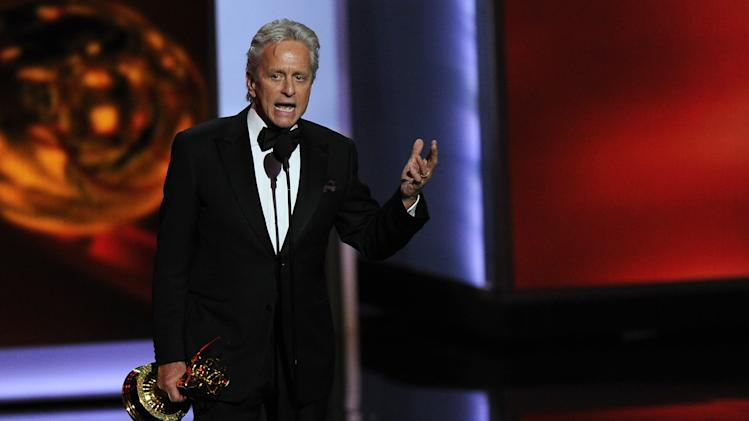 "Michael Douglas accepts the award for for outstanding lead actor in a miniseries or movie for his role in ""Behind The Candelabra"" at the 65th Primetime Emmy Awards at Nokia Theatre on Sunday Sept. 22, 2013, in Los Angeles. (Photo by Chris Pizzello/Invision/AP)"