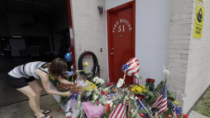 Shannon Neira places flowers at a makeshift memorial at Houston Fire Station 51, Saturday, June 1, 2013, in Houston. Four firefighters searching for people they thought might be trapped in a blazing Houston motel and restaurant Friday were killed when part of the structure collapsed and ensnared them, authorities said. (AP Photo/David J. Phillip)