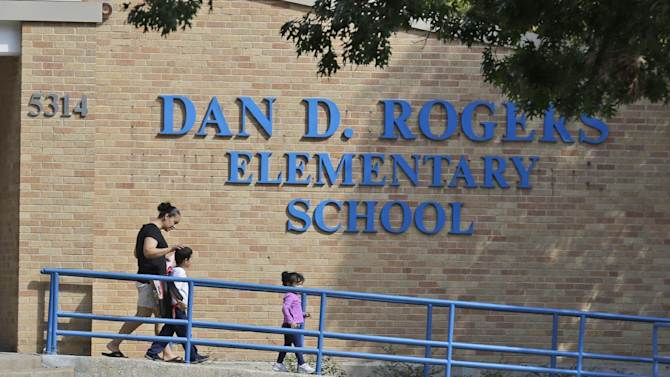 An adult walks with children outside Dan D. Roders Elementary School, Wednesday, Oct. 1, 2014, in Dallas, where children that were exposed to an Ebola infected family member attend classes. Authorities say five students who had contact with a man diagnosed with Ebola in Dallas are being monitored but are showing no symptoms of the disease. (AP Photo/LM Otero)