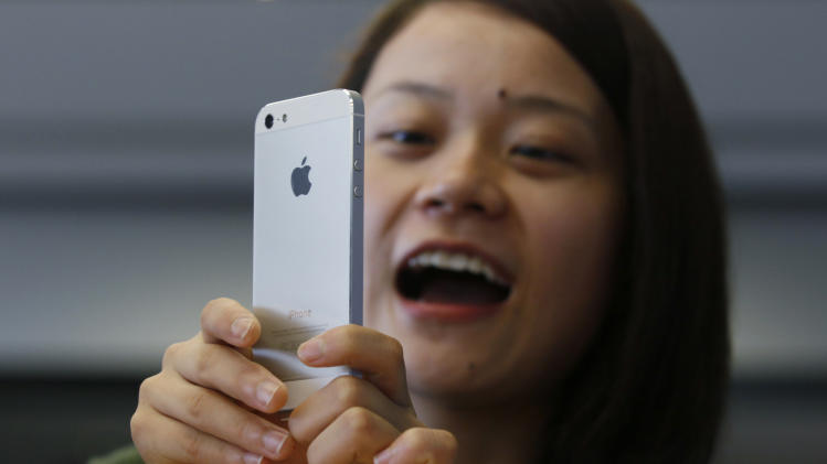 A customer tries on her new iPhone 5 at the Apple store in Hong Kong Friday, Sept. 21, 2012. Apple's Asian fans jammed the tech juggernaut's shops in Australia, Hong Kong, Japan and Singapore to pick up the latest version of its iPhone. (AP Photo/Kin Cheung)
