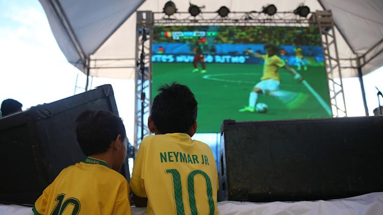 A couple of young soccer fans, watch on a giant screen television  Brazil play Cameroon in the soccer World Cup match, in Manaus, Brazil, Monday, June 23, 2014. Brazil's Neymar scored twice in the first half to lead Brazil to a 4-1 win over Cameroon on Monday, helping the hosts secure a spot in the second round of the soccer World Cup