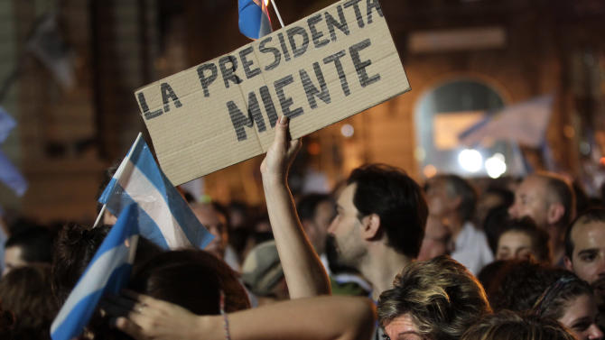 "A protester holds up a sign that reads in Spanish ""the president lies"" during a march against Argentina's President Cristina Fernandez in Buenos Aires, Argentina, Thursday, Nov. 8, 2012. Angered by rising inflation, violent crime and high-profile corruption, and afraid Fernandez will try to hold onto power indefinitely by ending constitutional term limits, the protesters banged pots and marched on the iconic obelisk in Argentina's capital. Protests also were held in plazas nationwide and outside Argentine embassies and consulates around the world. (AP Photo/Victor R. Caivano)"