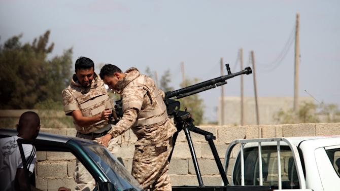 Soldiers from the Libyan National Army get ready to enter Rafallah al-sahati Islamic Militia Brigades compound, one of the compound buildings can be seen behind the wall, in Benghazi, Libya, Saturday, Sept. 22, 2012.  (AP Photo/Mohammad Hannon)