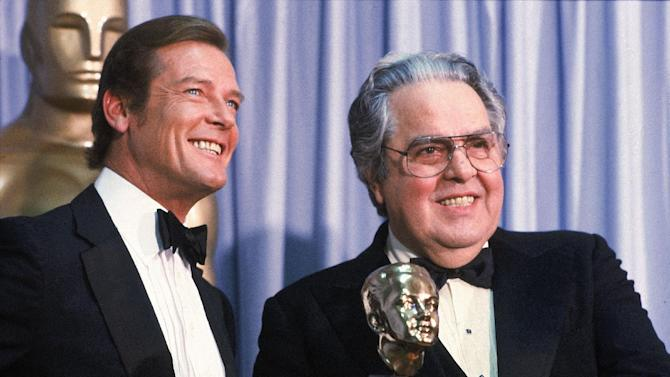 """FILE - In this March 29, 1982 file photo, Albert """"Cubby"""" Broccoli, producer of the """"James Bond"""" series, holds the Thalberg Award he received for his work at the Academy Awards, in Los Angeles.  Roger Moore, left, British actor who plays secret agent 007 James Bond, made the presentation.  (AP Photo/Reed Saxon, File)"""