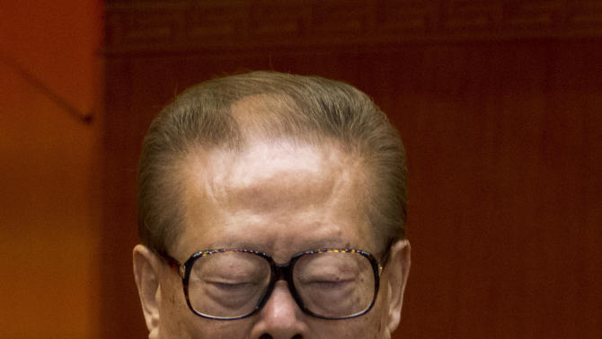 FILE - In this Nov. 8, 2012 file photo, former Chinese President and Chinese Communist Party general secretary Jiang Zemin claps while Chinese President Hu Jintao, unseen, reads a work report during the opening session of 18th Communist Party Congress at the Great Hall of the People in Beijing, China. The influential Jiang has been moved down the top leadership's pecking order, at least in public, as the ruling Communist Party prepares for the final stages of a generational handover in power. (AP Photo/Alexander F. Yuan, File)