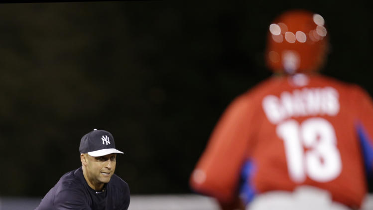 New York Yankees shortstop Derek Jeter (2) tosses to the second baseman to put out Philadelphia Phillies' Freddy Galvis (13) in a fourth-inning fielder's choice in a spring training baseball game in Tampa, Fla., Wednesday, March 13, 2013. (AP Photo/Kathy Willens)