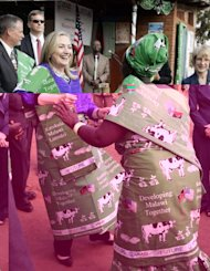 US Secretary of State Hillary Clinton (L) dances with the Chairperson of the Lumbadzi Milk Bulking Group, Emmie Phiri, in Lilongwe, Malawi. Clinton met schoolgirls and Africa&#39;s second woman president during an unprecedented visit to Malawi Sunday before jetting to South Africa to visit Nelson Mandela