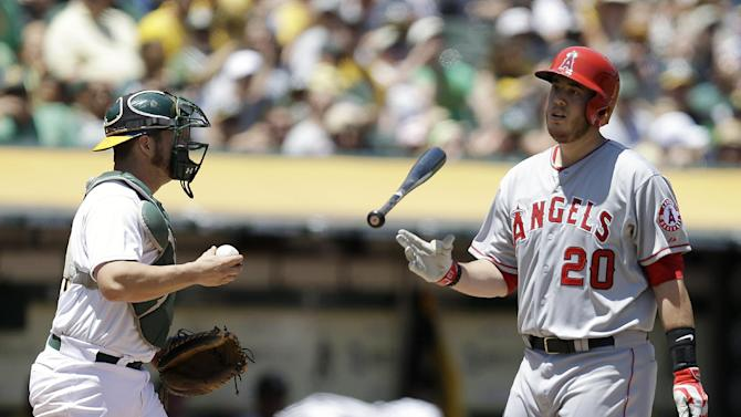 Los Angeles Angels' C.J. Cron, right, flips his bat after striking out to Oakland Athletics' Sonny Gray in the second inning of a baseball game, Sunday, June 1, 2014, in Oakland, Calif. At left is Athletics catcher Stephen Vogt. (AP Photo/Ben Margot)