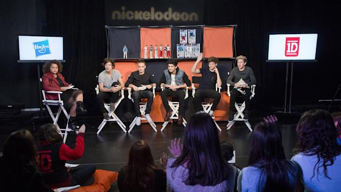"Members of worldwide musical sensation One Direction, from right to left, Niall Horan, Louis Tomlinson, Zayn Malik, Liam Payne and Harry Styles with moderator Rachel Crow answer questions about their Hasbro dolls from the winners of Nickelodeon's ""Your Moment with 1D"" sweepstakes at an exclusive fan event on Monday, Nov. 26, 2012 in New York. (Photo by Charles Sykes/Invision for Hasbro/AP Images)"