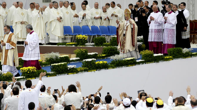 "Pope Benedict XVI, left, waves after celebrating a Mass in Bresso, near Milan, Italy, Sunday, June 3, 2012. Pope Benedict XVI has celebrated an open-air Mass before some 850,000 followers as part of three days of activities in Milan aimed at showing support for families. The pope in his homily Sunday took issue with modern economic thinking that he said ""creates ferocious competition, strong inequalities, degradation of the environment"" and reduces family relationships ""to fragile convergences of individual interests"" that undermine the social fabric. (AP Photo/Antonio Calanni)"