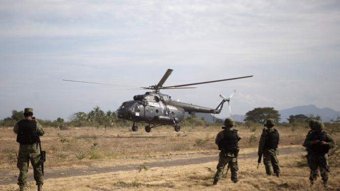 A military helicopter transports a group of vigilantes to a shootout investigation in La Ruana, Michoacan