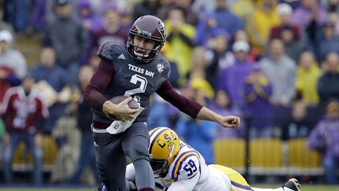 In this Nov. 23, 2013, file photo, Texas A&M quarterback Johnny Manziel (2) scrambles to avoid a tackle by LSU defensive end Jermauria Rasco (59) during the first half of an NCAA college football game in Baton Rouge, La. Manziel could be the answer to Cleveland's prayers at quarterback. The polarizing and popular Texas A&M star will likely be available when the Browns pick fourth in next week's NFL draft. But can they handle the Johnny Football Circus?