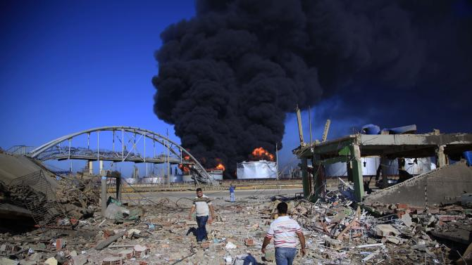 People walk at a damaged site after a explosion as flames rise over the Amuay refinery near Punto Fijo, Venezuela, Sunday, Aug. 26, 2012. Venezuelans who live next to the country's biggest oil refinery said they smelled a strong odor of sulfur hours before a gas leak ignited in an explosion on Saturday that killed at least 39 people and injured more than 80. (AP Photo/Ariana Cubillos)