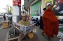 A man reads a state-run newspaper as a Buddhist monk walks past to collect morning alms in Yangon, Myanmar, Tuesday, March 12, 2013. An eagerly awaited official report has confirmed that police in Myanmar used smoke bombs that contain phosphorus during a crackdown on anti-mine protesters last year that left 108 people with burns, mostly Buddhist monks. The report also recommended the controversial Chinese-backed project continue. (AP Photo/Khin Maung Win)
