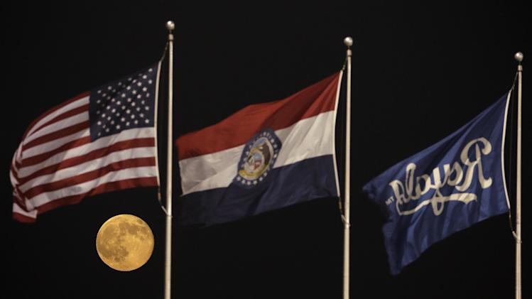 "A perigee moon, also known as a supermoon, rises beyond flags at Kauffman Stadium during a baseball game between the Kansas City Royals and the Detroit Tigers, Saturday, July 12, 2014. The phenomenon, which scientists call a ""perigee moon,"" occurs when the moon is near the horizon and appears larger and brighter than other full moons. (AP Photo/Charlie Riedel)"