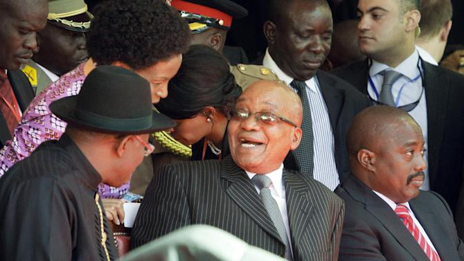 South African President Jacob Zuma, center, laughs with Nigerian President Goodluck Jonathan, left, as Congo's President Joseph Kabila, right, observes the proceedings at the inauguration of Kenya's President Uhuru Kenyatta in Kasarani, near Nairobi in Kenya Tuesday, April 9, 2013. Uhuru Kenyatta, 51, the son of Kenya's first president, was sworn in as Kenya's fourth president Tuesday in a stadium filled with tens of thousands of Kenyans and a dozen African leaders, becoming the second sitting African president to face charges at the International Criminal Court, over allegations he helped orchestrate the vicious tribe-on-tribe violence that marred Kenya's previous 2007 presidential election. (AP Photo/Khalil Senosi)