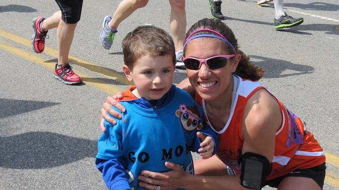 """This Monday, April 15, 2013 photo provided by Mark Fratto shows his wife, runner Courtney Fratto, and their son Gavin, 3, at mile 20 during the Boston Marathon in Boston. Fratto finished the race just seconds before the first bomb exploded. When the bomb went off just after she crossed the finish line, she ran for safety instead of to the injured. Fratto, a nurse who is the coordinator of intestinal transplants in the Pediatric Transplant Center at Boston Children's Hospital, wishes she could have reacted the way a number of others did. """"I could see there was mass casualties,"""" she said. """"I have this very horrible guilt that I didn't run and help them.'' (AP Photo/Mark Fratto)"""