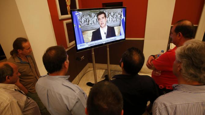 'No' supporters watch Greek Prime Minister Alexis Tsipras speaking on TV at Zappeion conference centre in Athens