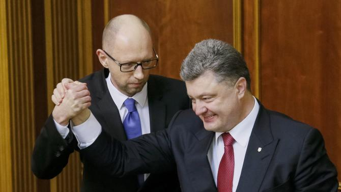 Ukraine's President Poroshenko congratulates newly appointed PM Yatseniuk during a session of the parliament in Kiev