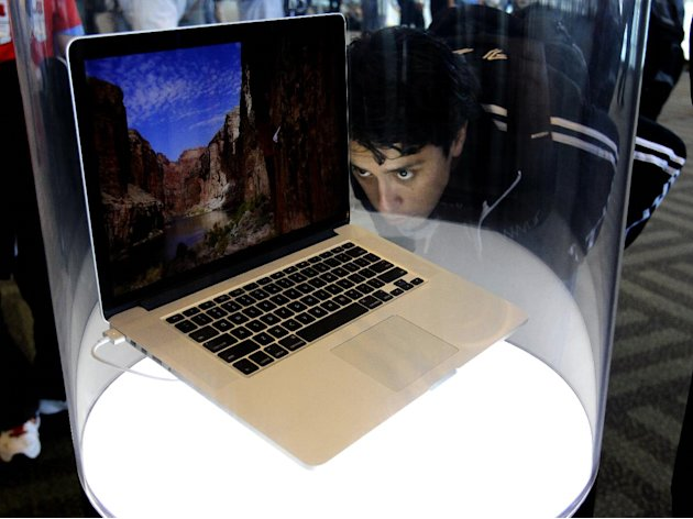 An attendee looks at the new MacBook Pro on display at the Apple Developers Conference in San Francisco, Monday, June 11, 2012. New iPhone and Mac software and updated Mac computers were among the hig