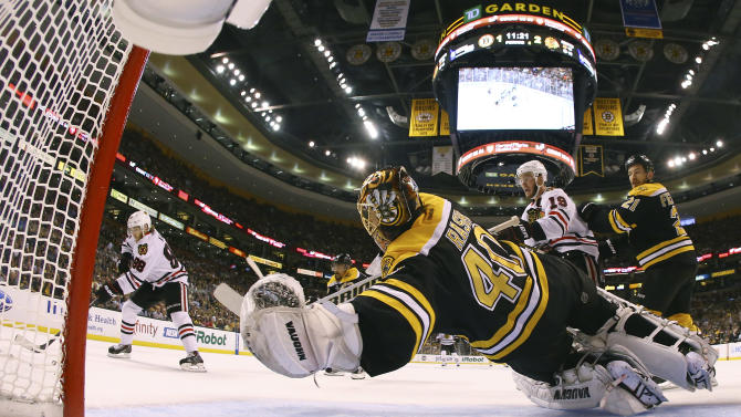Chicago Blackhawks right wing Patrick Kane, left, shoots as Boston Bruins goalie Tuukka Rask (40), of Finland, leaps in vain as Kane's shot scored during the second period in Game 4 of the NHL hockey Stanley Cup Finals Wednesday, June 19, 2013, in Boston. Blackhawks center Jonathan Toews (19), and Bruins defensemen Andrew Ference (21) watch. Chicago won 6-5 to even the series 2-2. (AP Photo/Harry How, Pool)