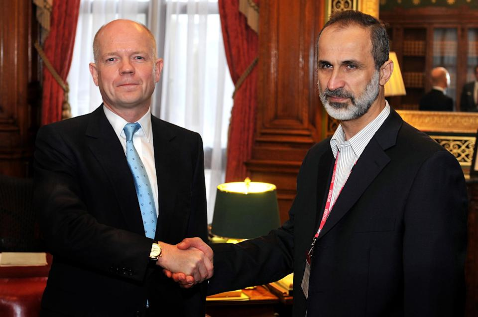 Britain's Foreign Secretary William Hague  shakes hands for the cameras with  head of the new Syrian National Coalition for Opposition and Revolutionary Forces Mouaz al-Khatib before a meeting on the continuing conflict in Syria, at the Foreign and Commonwealth office in Whitehall central  Friday Nov. 16, 2012. (AP Photo/ John Stillwell/Pool)
