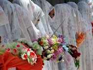 Afghan brides line up during a mass marriage ceremony in Herat province in 2009. An Afghan couple who fled the war-torn country to marry in Pakistan are being held in protective custody amid fears the bride&#39;s angry relatives will kill them, officials have told AFP