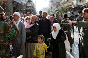 Residents are directed by soldiers in the town of Hejeira…