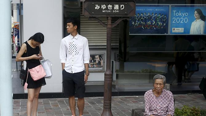 Tourists rest in shade outside Mizuho bank branch advertising its partnership with Tokyo 2020 Olympic Games in Tokyo