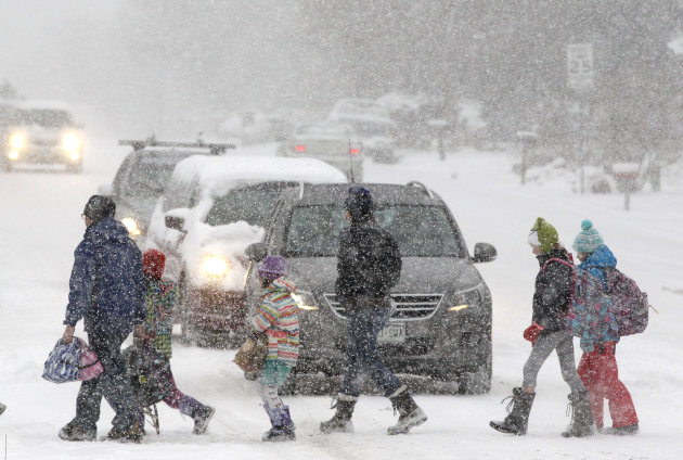 Elementary school students, some escorted by parents, cross a snowy street en route to school as a blizzard dropped snow over Boulder, Colo., Wednesday Dec. 19, 2012. A storm that has dumped more than