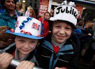 <p>Children wearing homemade crowns await the arrival of Britain's Queen Elizabeth II at St Macartin's Church of Ireland Cathedral in Enniskillen, Northern Ireland, on Tuesday. The queen shook hands with former IRA commander Martin McGuinness on Wednesday in a landmark moment in Northern Ireland's peace process, Buckingham Palace said.</p>