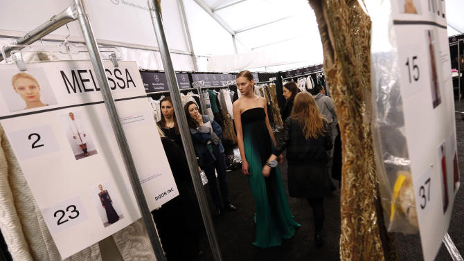 A model has her dress worked on backstage before the Monique Lhuillier Fall 2013 collection is modeled during Fashion Week, Saturday, Feb. 9, 2013 in New York.  (AP Photo/Jason DeCrow)