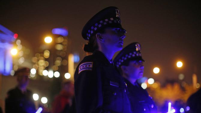 Chicago Police officers hold lightsticks as the names of officers killed in the line of duty are read out at the 11th Annual Chicago Police Memorial Foundation's Candlelight Vigil in Chicago