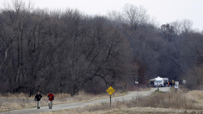 Law enforcement officials walk down a gravel road near the Seven Bridges Wildlife Area, Thursday, Dec. 6, 2012, in Readlyn, Iowa. Family members of missing cousins Lyric Cook, 10, and Elizabeth Collins, 8, who disappeared in July while riding their bikes in Evansdale, Iowa, are waiting to hear whether the two bodies discovered by hunters in the park on Wednesday are the two missing girls. (AP Photo/Charlie Neibergall)
