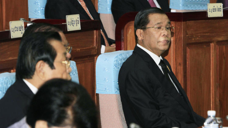 Cambodian Prime Minister Hun Sen, right, sits inside the session hall of the National Assembly with lawmakers from his Cambodian People's Party, in Phnom Penh, Cambodia, Tuesday, Sept. 24, 2013. Ruling party lawmakers in Cambodia's parliament have named Hun Sen prime minister for another five-year term. (AP Photo/Heng Sinith)
