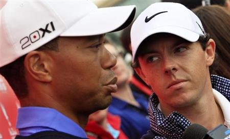 Rory McIlroy of Northern Ireland (R) looks at Tiger Woods of the U.S. during an interview ahead of the Abu Dhabi Golf Championships January 15, 2013. REUTERS/Ahmed Jadallah