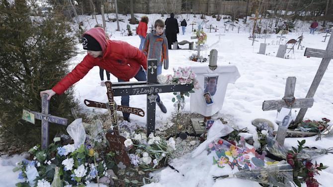 Jessica Garvey, of Woonsocket, R.I., front, steadies a cross at the site of the deadly nightclub fire in West Warwick, R.I., Wednesday, Feb. 20, 2013. Relatives and friends of the 100 people killed in the blaze at the The Station nightclub are gathering at the site on its 10th anniversary. The Feb. 20, 2003 fire was started when pyrotechnics for the hard rock band Great White ignited flammable foam that had been installed as soundproofing. (AP Photo/Steven Senne)